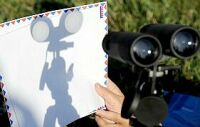 Projecting the Sun's image using a pair of binoculars. Click for larger version, 13 KB (Image: Robyn Beck/AFP/Getty Images/The Guardian)